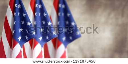 Three American flags in front of blurred brown background #1191875458