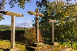 Three ancient crosses on monastery yard. Stone old crucifix. Catholic monastery landmark. Christianity symbols. Medieval cemetery. Crosses on the hill. Sunny day on Camino de Santiago.