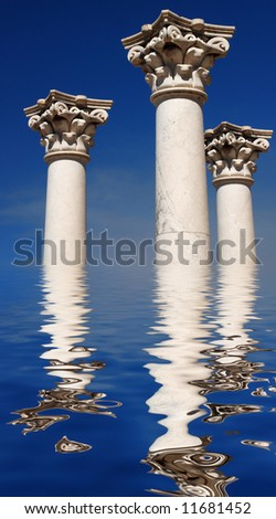 Three ancient greek pillars against a blue sky  reflecting in water