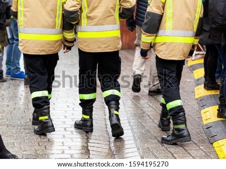 Three anonymous fireman in yellow reflective uniforms and black boots and trousers walking away from the camera on the crowdy street, back side, legs. Generic uniformed services vests abstract concept