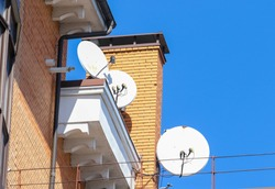 Three antennas to receive satellite signal on the roof of a residential building