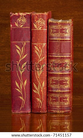 Three antique red leather bound  books standing up on a polished wooden shelf.