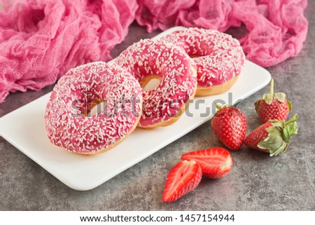 Three appetizing donuts in pink glaze lie on a white plate on a gray background. Junk food. #1457154944
