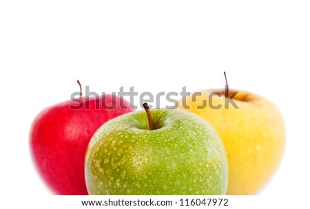 Three apples, green, red and yellow with water drops