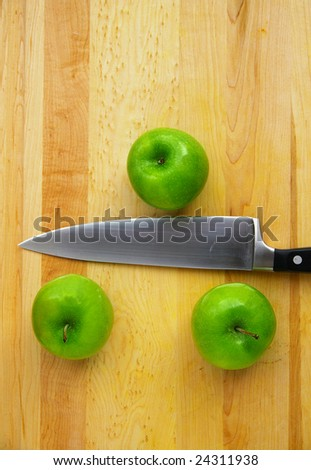 three apples on a cutting board, with a knife