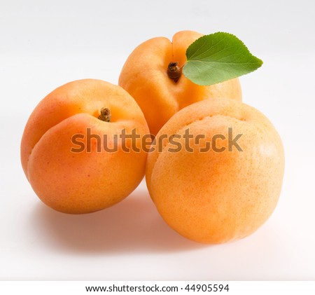 three apricots on white background