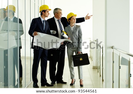 Three architects standing in office building and interacting