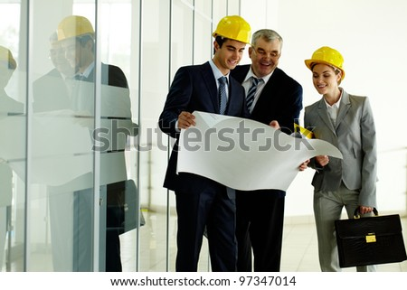 Three architects standing in office building and planning work