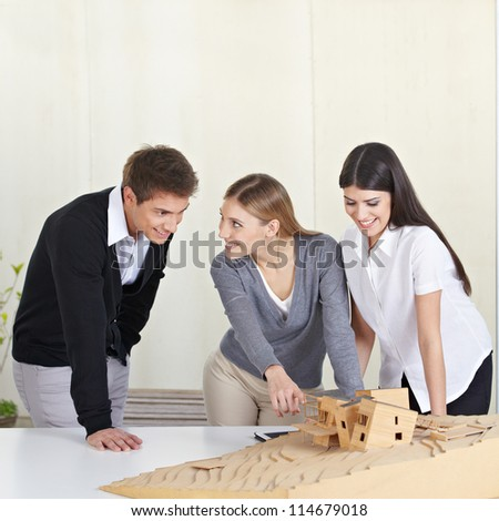 Three architecture students discussing 3D building model on desk