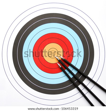 Three arrows aiming to the center of an archery target