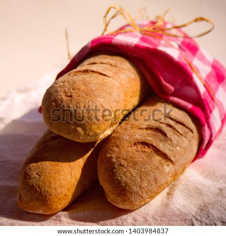 three artisan breads, tied with checkered napkin, in the sun.