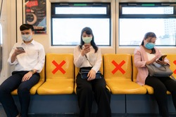 Three Asian people wearing mask sitting in subway distance for one seat from other people keep distance protect from COVID-19 viruses and people social distancing  for infection risk