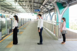 Three Asian people wearing mask standing distance of 1 meter from other people keep distance protect from COVID-19 viruses and people social distancing  for infection risk