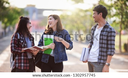 Three Asian  Scholarship Students smile and fun in park at university after learning in classroom. Life of studying and friendship, Overseas students concept.