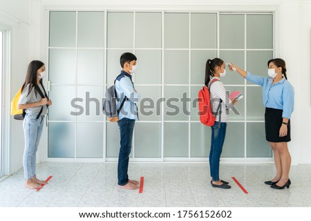 Three Asian student wearing mask standing distance of 6 feet from other people keep distance while teacher using thermometer temperature screening student for fever while student coming back to school