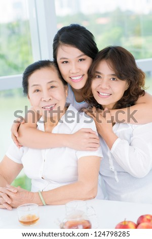 Three asian women sitting and looking at camera
