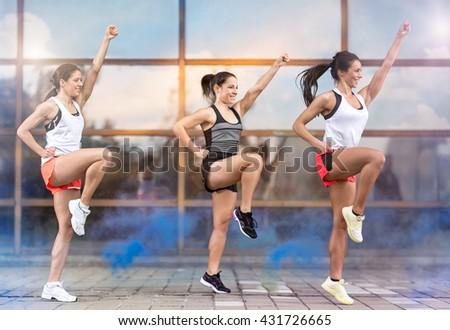 Three athletic girls doing aerobic exercises outside