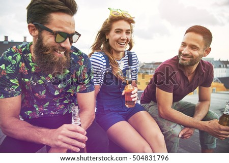 Three attractive and young adult friends drinking from open beer bottles together on roof in urban setting during summer