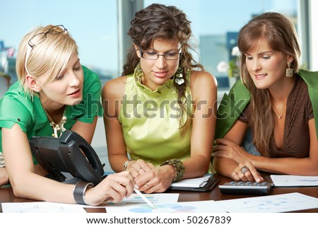 Three attractive businesswomen sitting at meeting room, discussing financial charts on table.