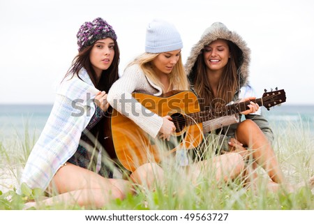 Three attractive young women sitting on the beach bundled up from the cold. One is playing a guitar. Horizontal shot.