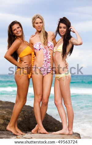 Three attractive young women wearing bikinis are standing on the rocks at the beach with their arms around each other. Vertical shot.
