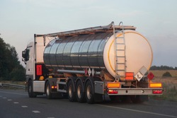 Three-axle semi truck with shiny chrome barrel tank with clear place on ADR sign moving on empty suburban asphalt highway road on a summer day on blue sky, dangerous cargo logistics, back side view
