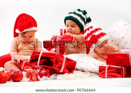 Three babies in xmas costumes playing with gifts