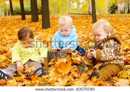 Three babies sitting on yellow leaves