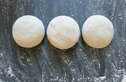 Three balls of fresh homemade wheat dough on kitchen table. Home baking. Dough for pizza cooking, pasta dumplings or bread.Horizontal.