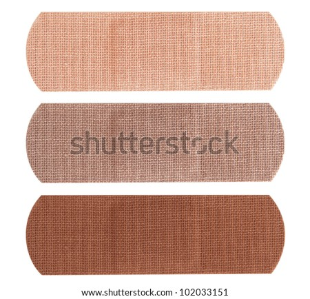 Three bandages in different skin colors isolated on white background.