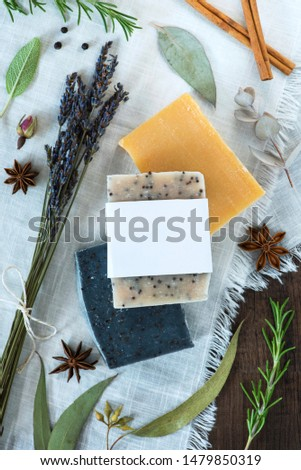 three bars of soap on a white cloth with natural ingredients, handmade soap with blank label, mockup label flat lay, rosemary, eucalyptus, star anise, lavender, peppercorns, cinnamon, rosebud, sage #1479850319
