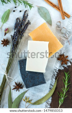 three bars of soap on a white cloth with natural ingredients, stack of handmade soaps flat lay, rosemary, eucalyptus, star anise, lavender, peppercorns, cinnamon, rosebud, sage #1479850313