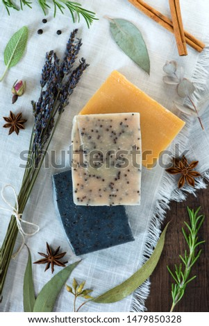 three bars of soap on a white cloth with natural ingredients, stack of handmade soaps flat lay, rosemary, eucalyptus, star anise, lavender, peppercorns, cinnamon, rosebud, sage #1479850328
