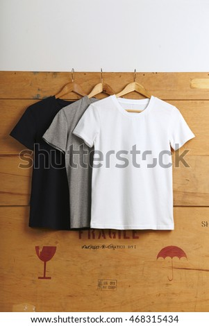 Three basic blank t-shits - black, grey and white, presented on wooden cargo box background Close view
