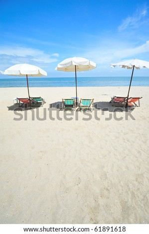 Three beach chairs with umbrellas
