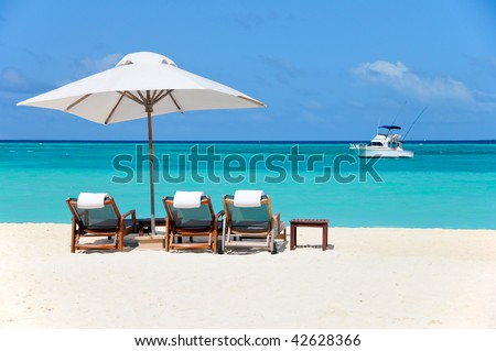 three beach chairs with white umbrella and yacht at ocean front
