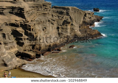 Three beach goers stand besides the sand stone cliffs on Green Sand Beach.  Their minute size in comparison to the cliffs give some scale to their tremendous size.  Aqua blue waters frame image.