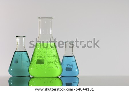 three beakers with green and blue liquid