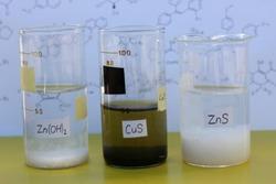 Three beakets with insoluble substances: white zinc hydroxide, black copper sulfide, white zinc sulfide.