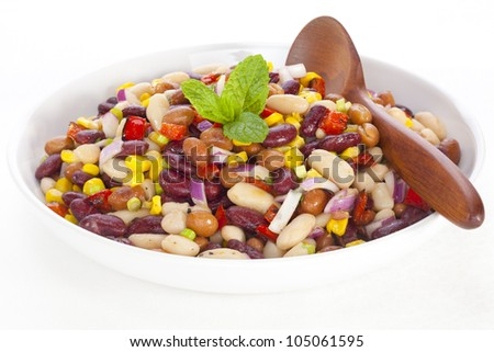 Three bean salad with sweetcorn, roasted red peppers and red onion in a vinaigrette dresing.