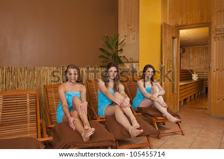 three beautiful and smiling young women sitting on loungers in front of a sauna