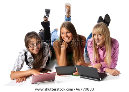Three beautiful cheerful girlfriends lay with laptops on a white background. Students.