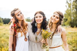 Three beautiful cheerful hippie girls, best friends, the outdoors, trendy hairstyles, feathers in her hair, white dress, tattoo flash, gold accessories, Bohemian, bo-ho style blonde, brunette, redhead