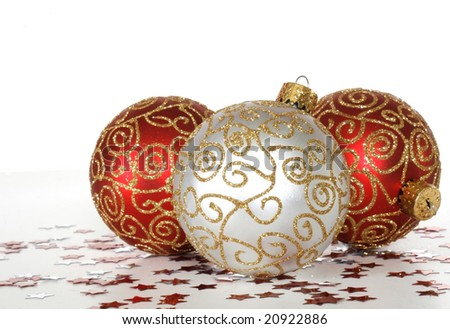three beautiful christmas ornaments, star confetti on white background with copy space