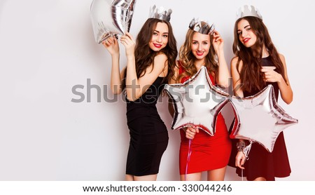 Three beautiful elegant women celebrate birthday  and dancing. Best friends wearing black stylish evening dress, high heel shoes ,crown on head .Bright make up, red lips. Inside.