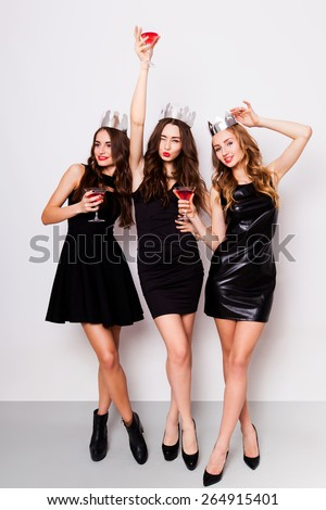 Three beautiful elegant women celebrate hen-party and drinking cocktails. Best friends wearing black  stylish evening dress,  high heel shoes ,crown on head .Bright make up, red lips. Inside.