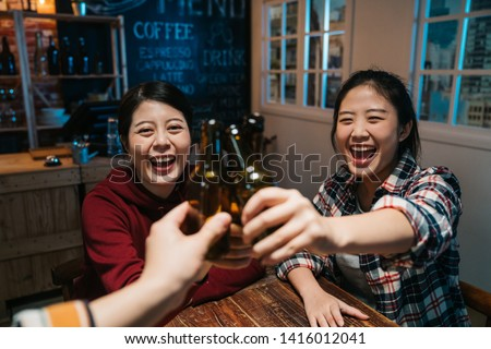 three beautiful female friends clinking bottles of beer and smiling while resting at night pub. group of happy young people cheers celebrating cheerful laughing sitting in late midnight dark bar. #1416012041