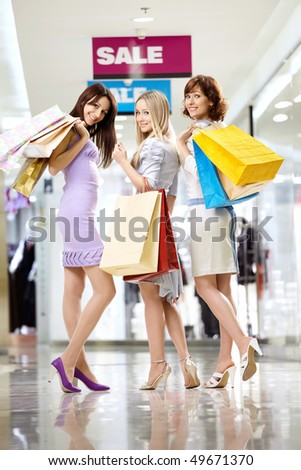 Three beautiful girlfriends in shop with bags