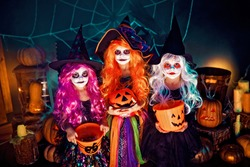 Three Beautiful girls in a witch costume. Funny sisters celebrate the holiday. Jolly children in carnival costumes ready for Halloween in halloween decorations