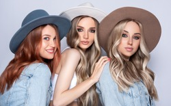 Three beautiful girls in hats  with hair coloring in ultra blond. Stylish hairstyle curls done in a beauty salon. Fashion, cosmetics and makeup